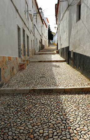 uphill: Stone paved street uphill to the castle, Estremoz, Alentejo, Portugal, South of Europe Stock Photo