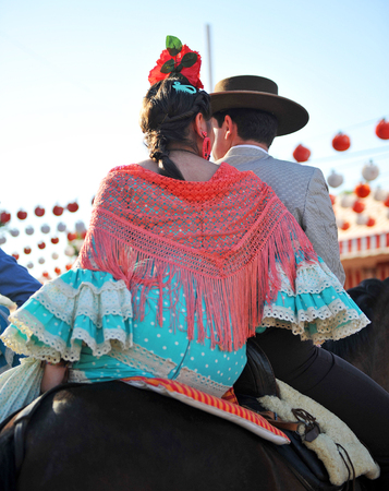 Feast in Spain, young couple riding in the Seville Fair, springtime