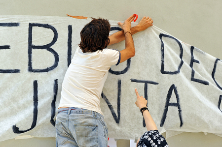 assemblies: Two people placing a banner on the wall, freedom of speech, popular demands, Spain Stock Photo