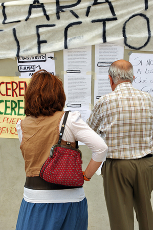 assemblies: Two seniors reading manifestos and banners on the wall, popular expression, the demands of people, Spain