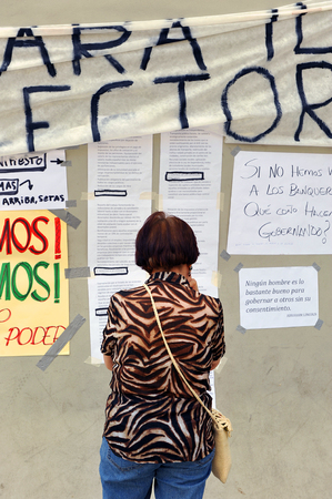 assemblies: A senior woman reading manifestos and banners on the wall, popular expression, the demands of people, Spain