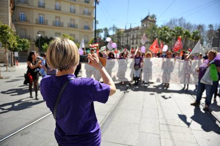 mujer golpeada: Demostración en el día de la mujer trabajadora, Sevilla, España Editorial