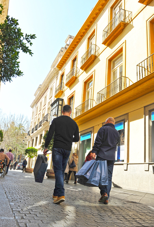 youngs: Two men with shopping bags in a shopping street