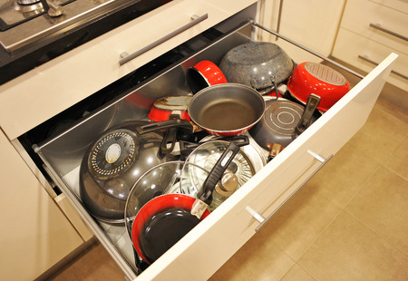 dripping pan: Drawer kitchen cabinet full of all kinds of pots and pans Stock Photo