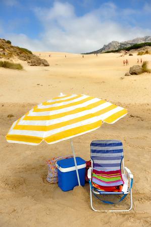 Umbrella, chair and fridge on the dunes of Bolonia beach, Tarifa, Cadiz province, Spain Stock Photo