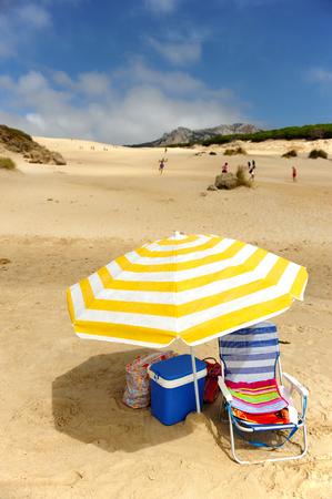 sun bathers: Umbrella, chair and fridge on the dunes of Bolonia beach, Tarifa, Cadiz province, Spain Stock Photo