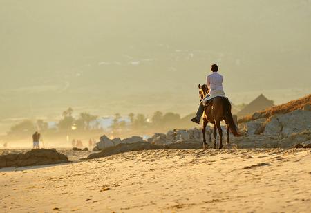 tarifa: Walk on horseback on the beach of Bolonia, summer vacation, Tarifa, Cadiz province, Spain Stock Photo