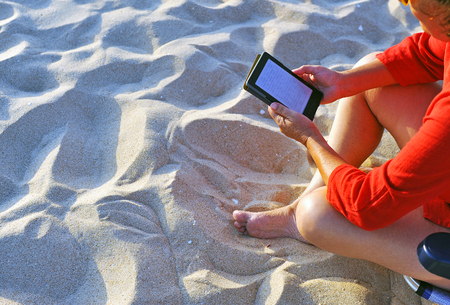 Woman on chair reads the ebook on the beach
