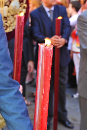 holy thursday: Red lighted candle in hand, Corpus Christi, religious celebration in Seville, Andalusia, Spain