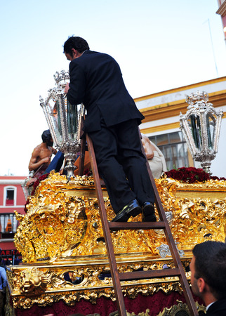 Man lighting the lanterns of a paso, Holy Week in Seville, Andalusia, Spain