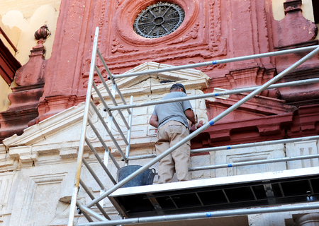 Mason cleaning the stone facade of a church in Seville, Spain 版權商用圖片 - 63648190