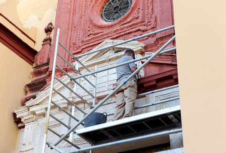bricklayer: Bricklayer cleaning the stone facade of a church in Seville, Spain Stock Photo