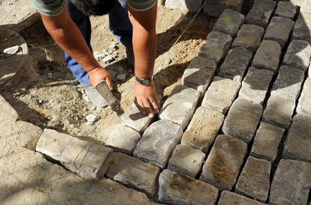 Workman paving a street with cobblestones