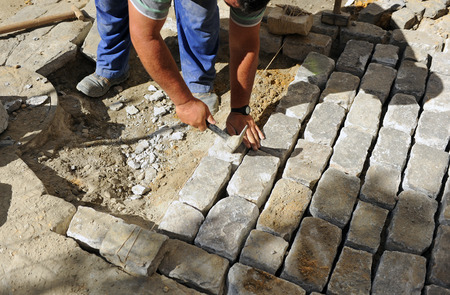 construction worker during  paving a street with cobblestones