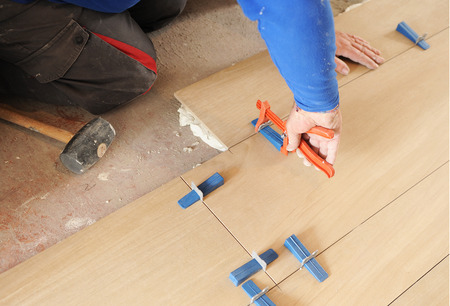 by placing: Bricklayer placing a porcelain tile floor in imitation of beechwood