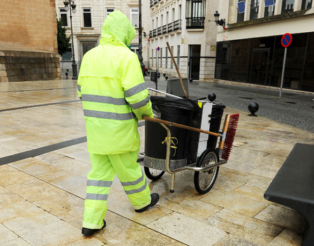 sweeper: Sweeper of municipal cleaning service working in the rain