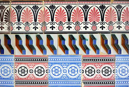 polychrome: composition of polychrome tiles (azulejos) of various designs reused, vintage decorative detail, Cartuja, Seville, Spain