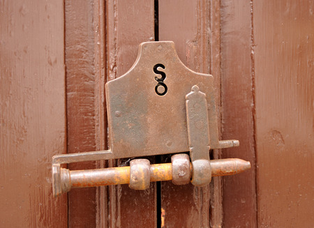 Old closed wooden door with bolt and key