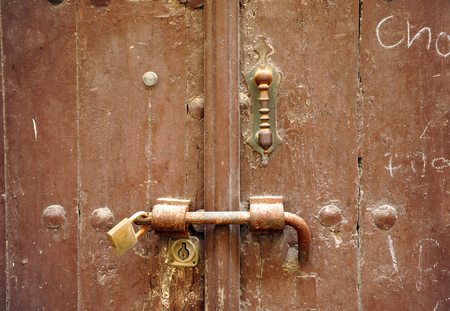 Old closed wooden door with bolt and padlock Imagens - 82076866