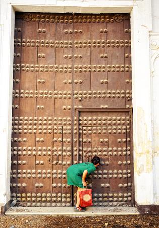 prying: woman looking through the keyhole, female curiosityhole, female curiosity Stock Photo