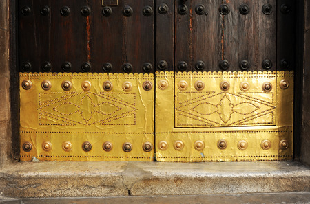 buffing: Ancient wooden door and gilded brass of a spanish mansion, background