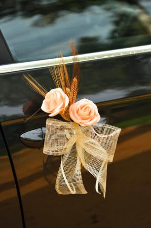 wedding day, bouquet of roses in bridal car door, honeymoon