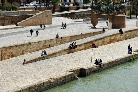 People walking and sunbathing on the Salt Dock (Muelle de la Sal), on the bank of the Guadalquivir River in Seville, Andalusia, Spain Banque d'images - 106711472