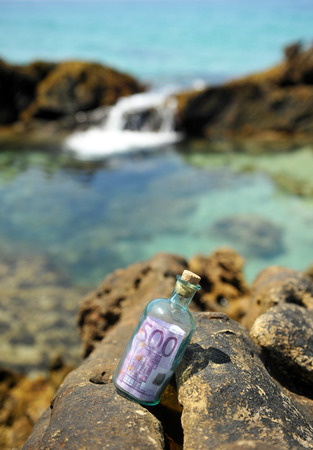 Old glass bottle with 500 euros in the sea rocks