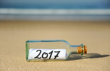 New year party, bottle with message on the beach, 2017