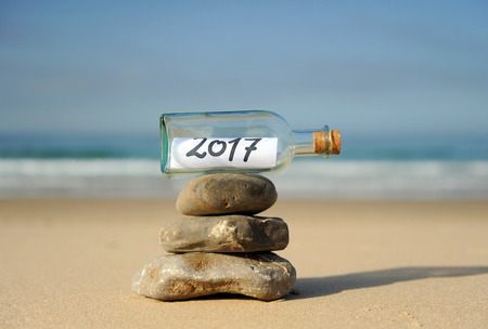 New year balance, bottle with message on the beach, 2017