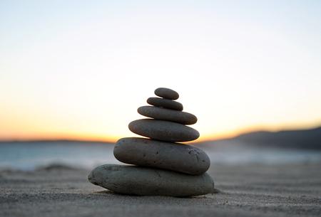 firmeza: pyramid of stones on the sand at sunset, zen spirit