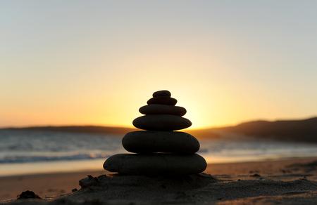 firmeza: Piedras del zen en la playa al atardecer Foto de archivo