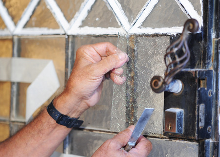 glazier: Glazier changing the crystals of an old door Stock Photo