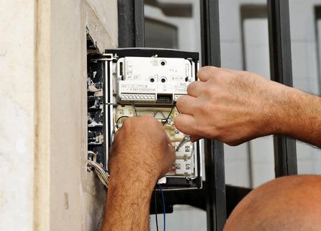 Technicien mettant le nouveau téléphone interphone sur la porte du bâtiment Banque d'images - 71924207
