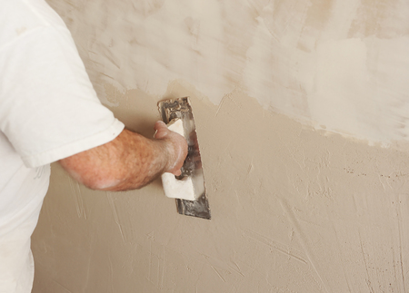 Bricklayer using the plastering trowel, wall plastered during house reform Banque d'images - 106978768