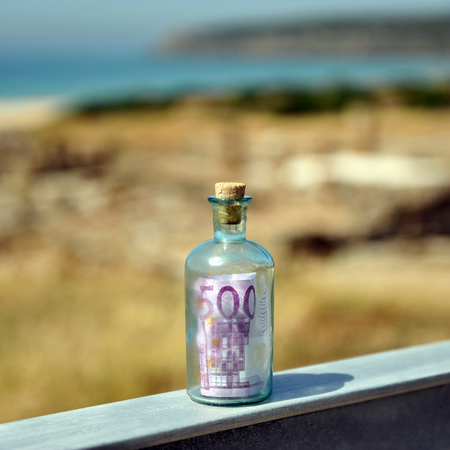 Old bottle with 500 euro inside on the landscape Stock Photo