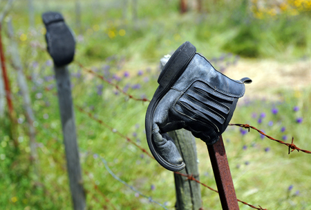 wire fence: Worn and abandoned boots after a long road Stock Photo
