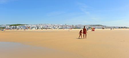 Father with his daughter walking in Bateles beach, Conil de la Frontera, coast of Cadiz, Andalusia, Spain