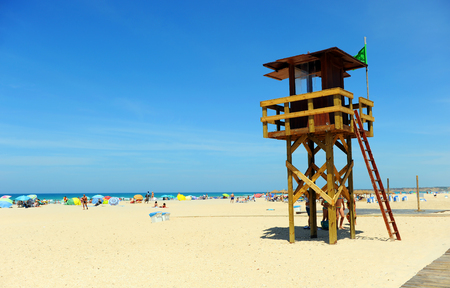 Watchtower with green flag on the beach of Bateles, Conil de la Frontera, Spain
