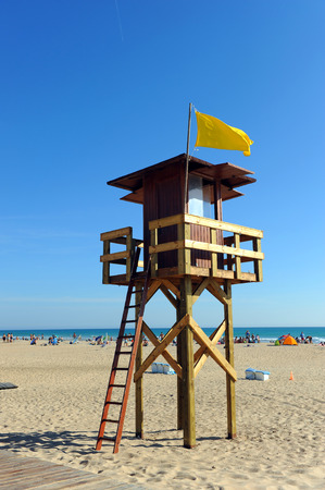 Watchtower with yellow flag on the beach of Bateles, Conil de la Frontera, Spain Editorial