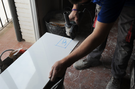 Mason by cutting the white glazed tiles with radial
