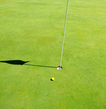 Hole and yellow ball in Golf Course, Andalusia, golf in Spain
