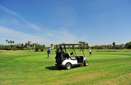 Buggy and players in Costa Ballena Golf course, Rota, Cadiz province, Spain