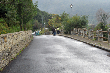 People walking alone along the road on the outskirts of Benamahoma village after rain, Andalusia, Spain Banque d'images - 106188435