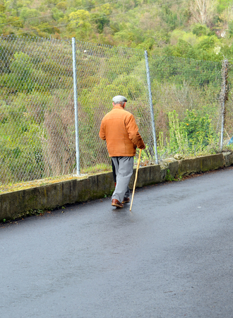 Elderly man walking alone along the road on the outskirts of Benamahoma village after rain, Andalusia, Spain Banque d'images - 106188438