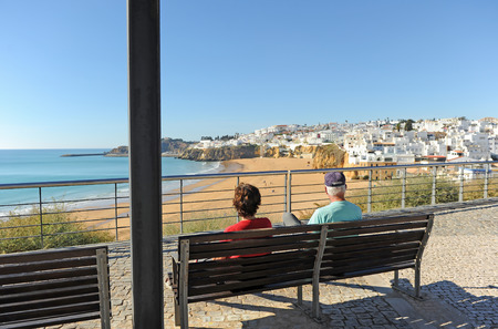 Couple of elderly tourists in the beach of Albufeira, beaches of Algarve, south of Portugal. Banque d'images - 106187970