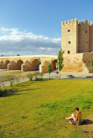 A girl drawing next to the Calahorra Tower and Roman Bridge of Cordoba with the Cathedral - Mosque in the background, Andalusia, Spain Banque d'images - 106712529
