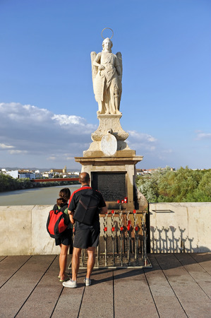 Couple of tourists before the altar with statue of archangel St. Raphael (San Rafael) on the Roman Bridge. Cordoba, Andalusia, Spain Banque d'images - 106712530