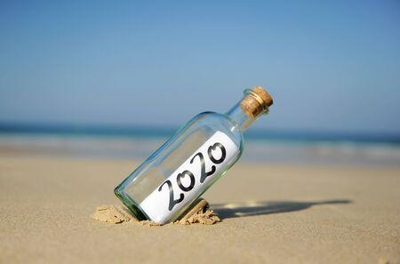 Feliz año nuevo 2020, mensaje en una botella en la arena de la playa. Concepto de vacaciones de verano Foto de archivo