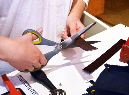 young craftswoman cutting a leather belt with scissors to attach the buckle Banque d'images
